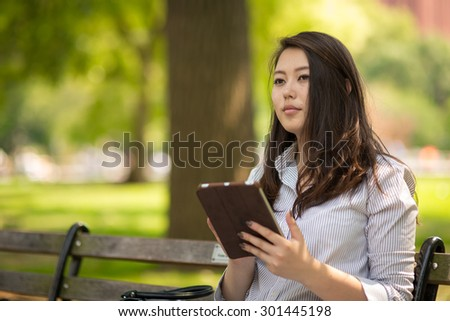 Young Asian woman sitting park bench using tablet pc computer