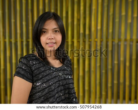Young Asian woman smiling against bamboo wood background
