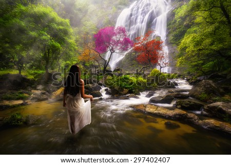 Young asian woman standing by a stream in the dreamy forest