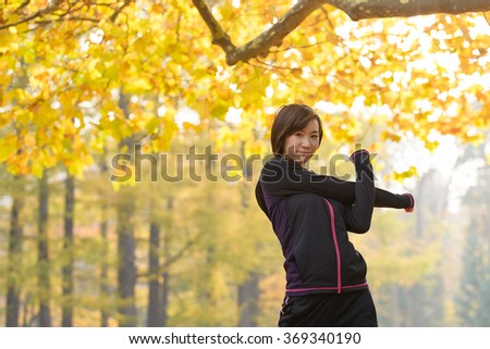 Young Asian woman stretching arms under the tree. - stock photo