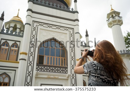 Young Asian woman take photo of Masjid Sultan, Singapore Mosque, in Arab Street, Raining day