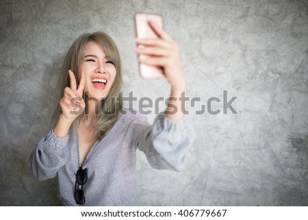 Young asian woman taking a selfie by her smart phone