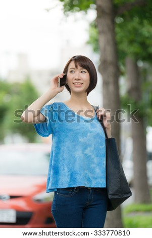 Young Asian woman talking with smart phone. - stock photo