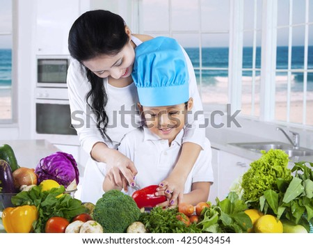 Young Asian woman teaches her son to prepare and cutting vegetables on the table in the kitchen