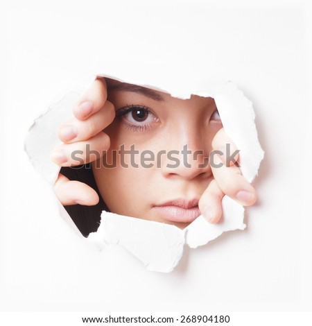 young asian woman tearing hole in paper wall to peek through - stock photo