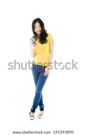 Young Asian woman text messaging on a mobile phone - stock photo