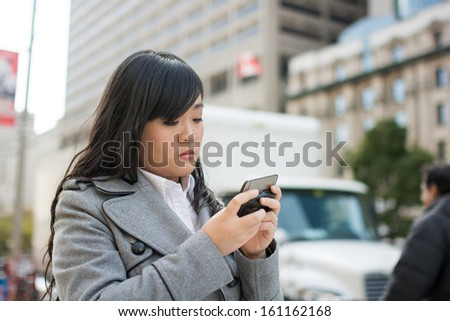 Young Asian woman texting and walking on a street in a large city - stock photo