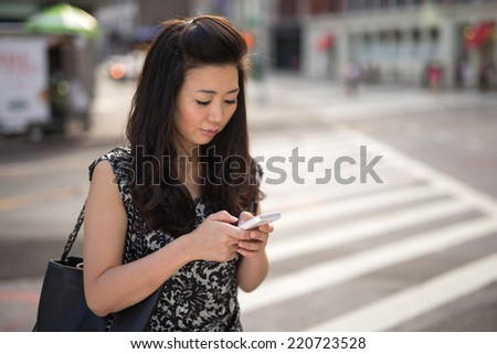 Young Asian Woman texting cellphone outdoor on city street