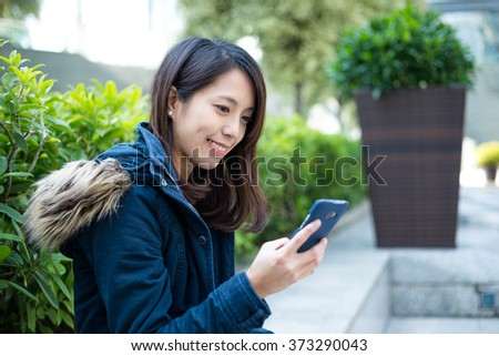 Young Asian woman texting on cellphone outdoor
