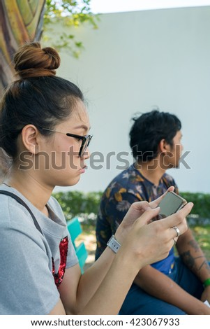 Young Asian woman texting smart phone with friend.