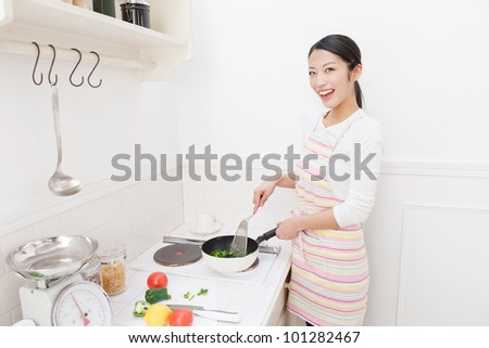 Young Asian woman to cook in the kitchen