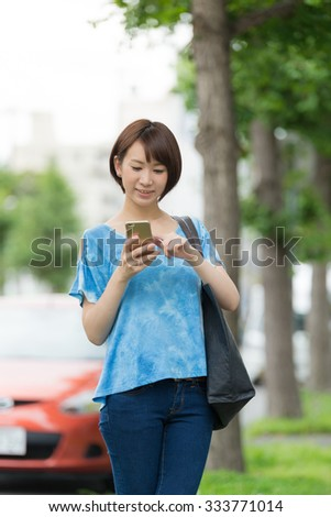 Young Asian woman using a smart phone. - stock photo