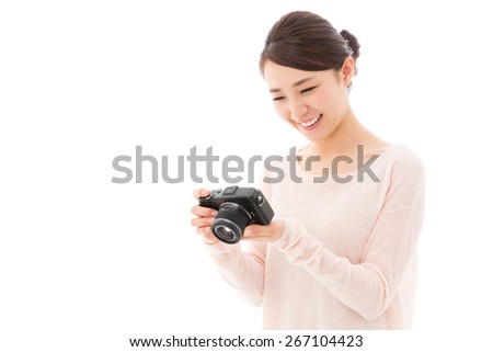 young asian woman using digital camera on white background
