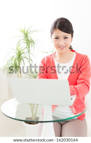 young asian woman using laptop computer in the cafe