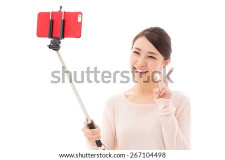 young asian woman using selfie stick on white background - stock photo