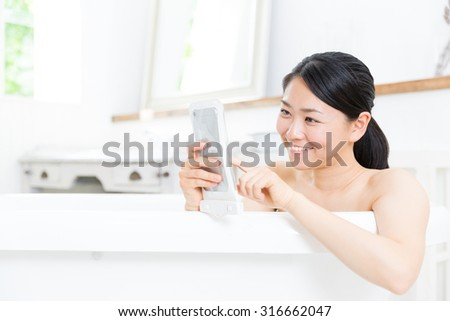 young asian woman using smart phone in the bathtub