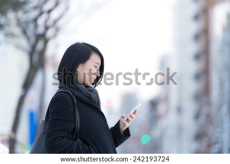 Young Asian woman using smart phone on a winter city. - stock photo