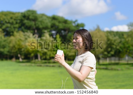 Young Asian woman walking in a park and listening to music