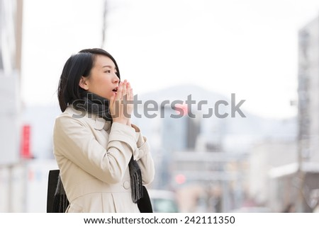 Young Asian woman walking in a winter city. - stock photo
