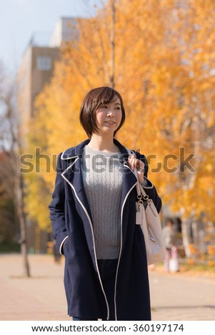 Young Asian woman walking in Autumn City. - stock photo