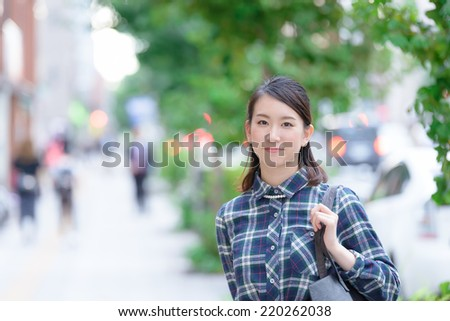 Young Asian woman walking on a city street. - stock photo