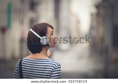 Young Asian woman walking on a street and listening to music. - stock photo
