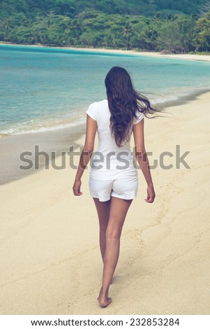 Young Asian woman walking on a tropical beach with her long hair blowing in the wind as she crosses the golden sand of a lush green bay on a hot summer day on her vacation - stock photo
