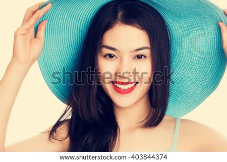 Young Asian woman wearing blue straw hat with expression of surprise, vintage tone style.