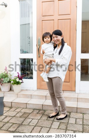 young asian woman with baby in entrance - stock photo