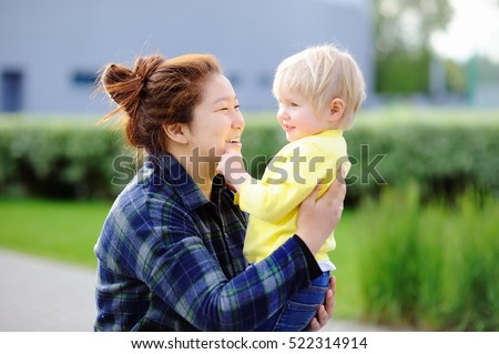 Young asian woman with cute caucasian toddler boy. Babysitting concept