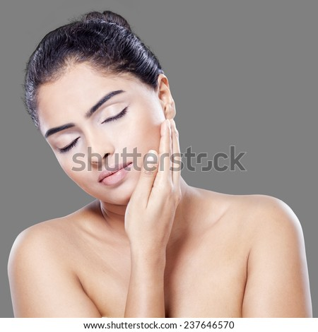 Young asian woman with healthy skin touching her face softly, shot in the studio against grey background - stock photo
