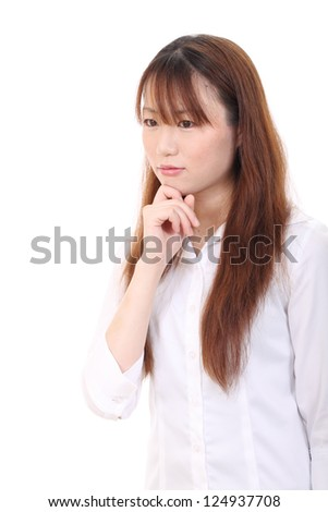 Young asian woman with her finger by her face - stock photo