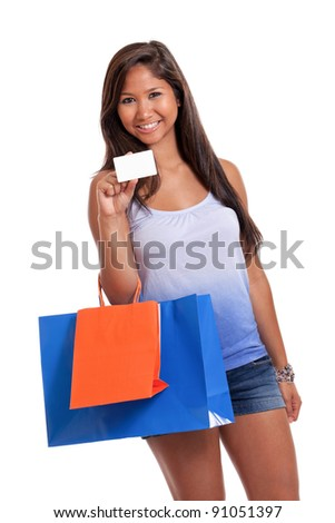 Young Asian woman with shopping bags and blank gift or credit card isolated on white - stock photo