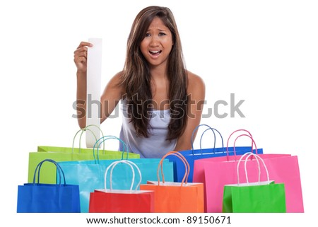 Young Asian woman with shopping bags shocked at her receipt after spending too much - stock photo