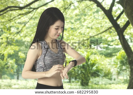 Young Asian woman with slim body, doing workout at the park and looking at her smart watch