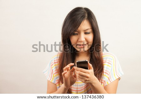 Young Asian woman woman text messaging