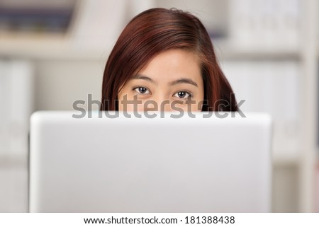 Young Asian woman working at a computer peering over the top of the screen at the camera with just her eyes visible - stock photo
