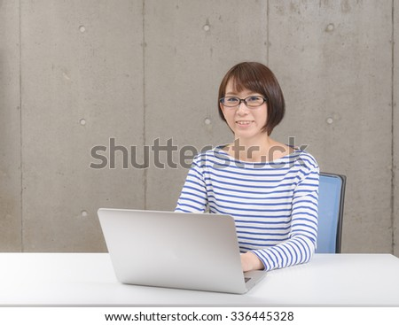 Young Asian woman working on a laptop computer. - stock photo