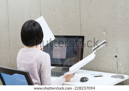 Young Asian woman working with a desktop computer.  - stock photo