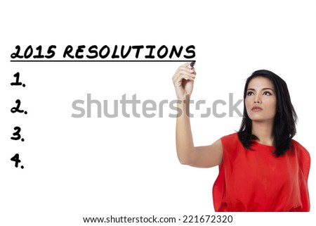 Young asian woman writes a list of resolutions in 2015, isolated over white background - stock photo