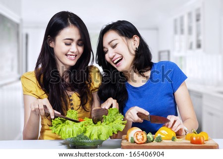 Young asian women prepare salad together in the kitchen - stock photo