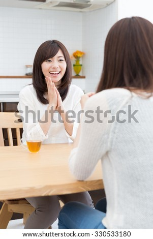 young asian women talking in the kitchen - stock photo