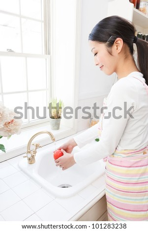 Young Asian women wash the tomatoes in the sink by the window - stock photo
