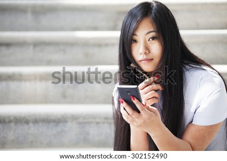 Young Asian women watch videos with mobile phones