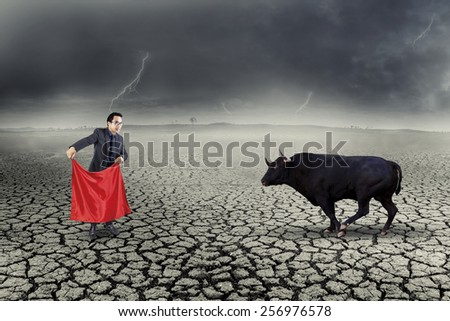 Young asian worker using a red cloth to play with a big bull outdoors - stock photo