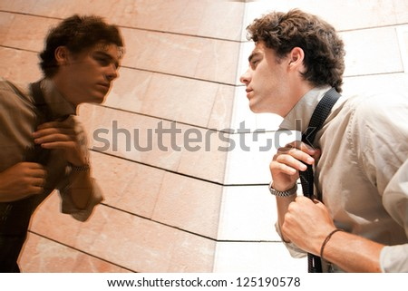 Young aspirational businessman doing up his tie knot in a golden mirror modern office building in the city. - stock photo