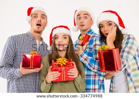 Young astonished people in santa hats holding presents - stock photo