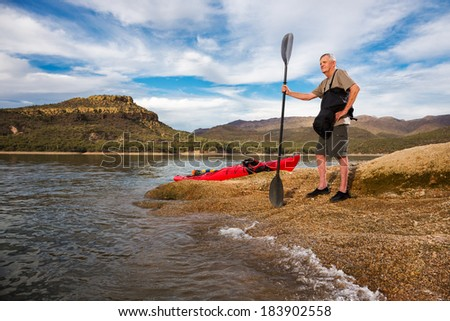 Young at Heart.  Senior Man Surveying the Lake Before a Paddle. A Rolling Wave Outlines the Shore. - stock photo