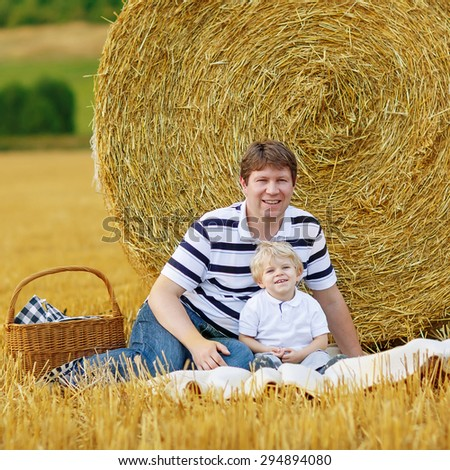 Young ather and little son, kid boy having picnic on yellow hay field in summer, outdoors. Family having fun together. - stock photo