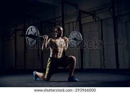 Young athlere training lunges with barbells - stock photo